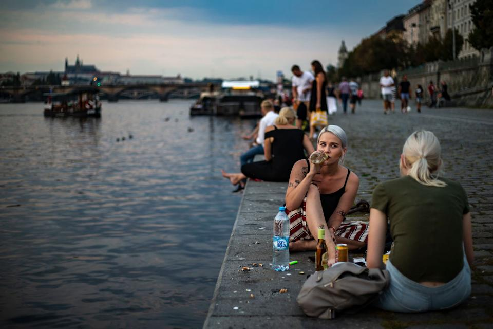Two woman sitting by the water with a crowd of people in the Czech Republic, which recorded its highest increase of coronavirus cases.