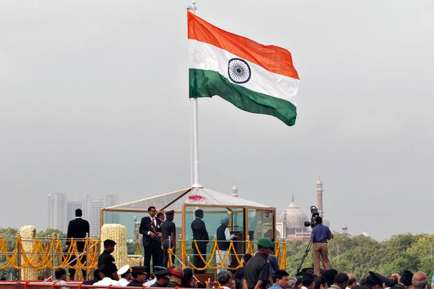 India's Prime Minister Manmohan Singh addresses the nation from a bullet-proof enclosure as Indian national flag flutters at the historic Red Fort during Independence Day celebrations in Delhi August 15, 2012. Singh forecast economic growth of more than 6.5 percent for this fiscal year on Wednesday, a more optimistic take than a recent spate of private projections that saw growth slowing to as low as 5.5 percent. REUTERS/Adnan Abidi