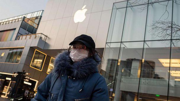 PHOTO: A woman wearing a protective face mask walks outside of a closed-off Apple Store in Beijing, Feb. 3, 2020. (Nicolas Asfouri/AFP/Getty Images)