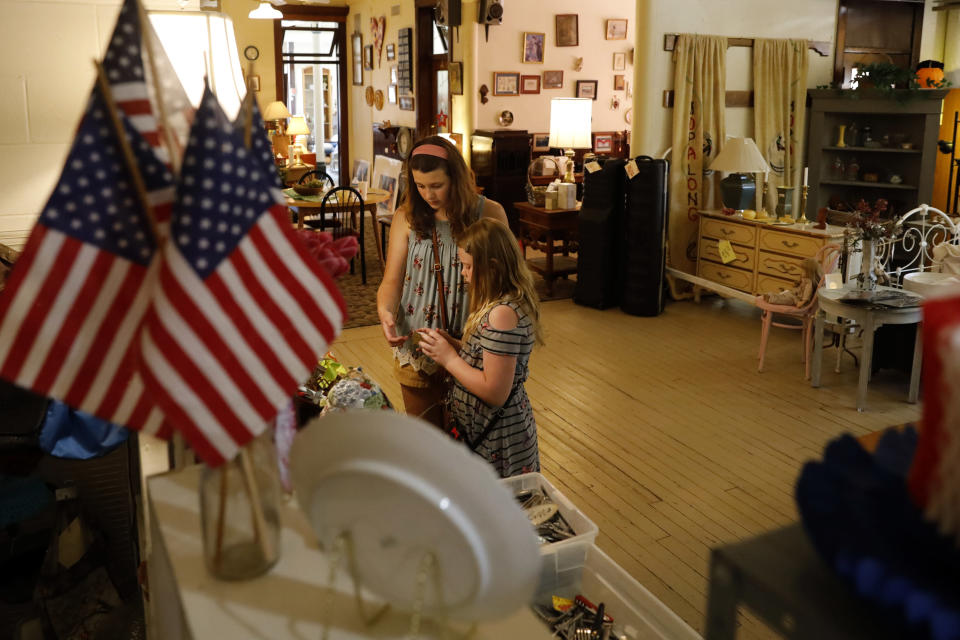 Lena Anderson left, and her sister Cora, look at merchandise at the Galesburg Antiques Mall, Wednesday, June 16, 2021, in Galesburg, Ill. (AP Photo/Shafkat Anowar)