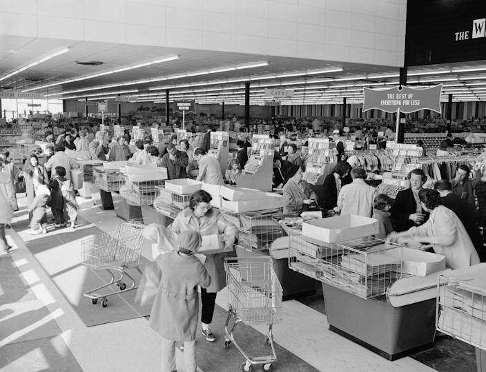 <p>Endless rows of cashiers serve the lines of customers at a busy supermarket.</p>