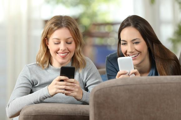 Two women looking at their phones.