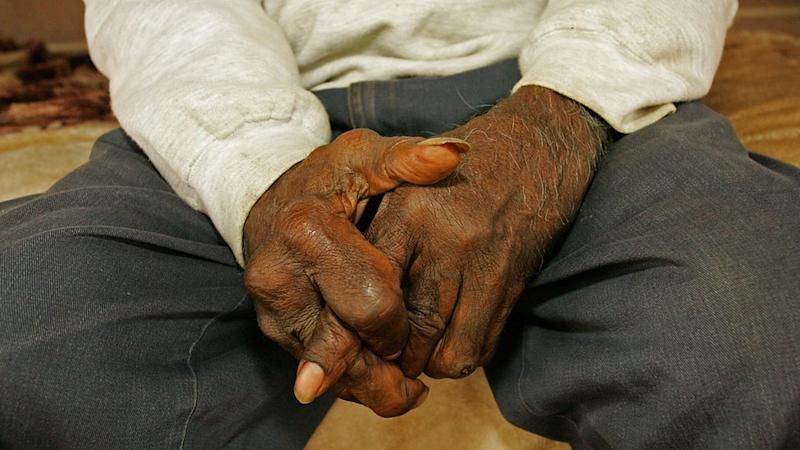 Man sits with hands clasped