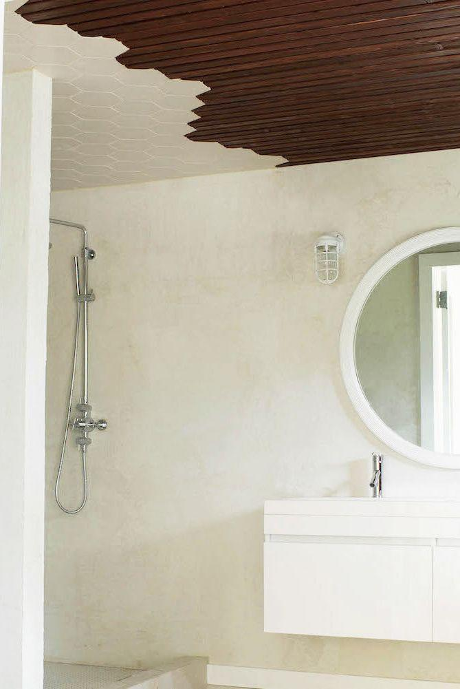 """<p>You don't need to use wild colors and prints to create a unique and playful bathroom. Take, for example, this neutral-hued space by <a href=""""https://leanneford.com/"""" rel=""""nofollow noopener"""" target=""""_blank"""" data-ylk=""""slk:Leanne Ford Interiors"""" class=""""link rapid-noclick-resp"""">Leanne Ford Interiors</a>. In lieu of a glass or curtain enclosure, the white hexagonal ceiling tiles meet the stained wood shiplap to visually separate the shower and the sink area, all the while, packing plenty of design punch. </p>"""