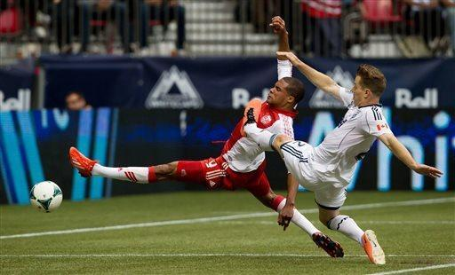 Portland Timbers' Ryan Johnson, left, of Jamaica, reaches for the ball off a pass as Vancouver Whitecaps' Jordan Harvey defends during the first half of an MLS soccer game in Vancouver, British Columbia on Saturday, May 18, 2013. (AP Photo/ The Canadian Press, Darryl Dyck)