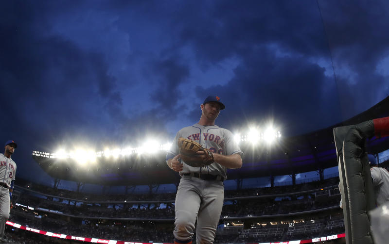 Clouds loom over SunTrust Park as New York Mets first baseman Pete Alonso (20) leaves the field after the fifth inning of a baseball game against the Atlanta Braves, Monday, June 17, 2019, in Atlanta. (AP Photo/John Bazemore)