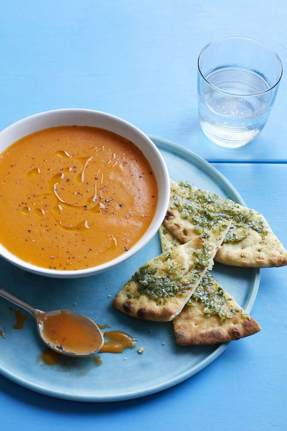 """<p>It takes less than half an hour to make this spiced tomato soup. Smother some fresh herbed butter on flatbread is the perfect accompaniment.</p><p><strong><em><a href=""""https://www.womansday.com/food-recipes/food-drinks/recipes/a59774/spiced-tomato-soup-flatbread-recipe/"""" rel=""""nofollow noopener"""" target=""""_blank"""" data-ylk=""""slk:Get the Spiced Tomato Soup with Flatbread recipe."""" class=""""link rapid-noclick-resp"""">Get the Spiced Tomato Soup with Flatbread recipe. </a></em></strong></p>"""