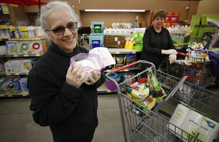 "Shopper Aviva Rosenbloom, 72, is thankful for toilet paper donated in single rolls by shopper Carol Wallace, right, who was able to grab a package early at the Grocery Outlet Bargain Market in Altadena as senior shoppers lined up before dawn outside Thursday morning. <span class=""copyright"">(Al Seib/Los Angeles Times)</span>"