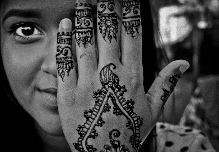 <p>A woman gets her hand painted with henna the night before the Muslin holiday Eid in September 2015, on 74th Street in Jackson Heights, Queens, N.Y., is filled with henna stands run by teens making few extra dollars. (Photo: Yunghi Kim/Contact Press Images) </p>
