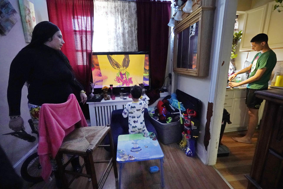 Isabel Miranda, left, speaks to her 4-year-old son, Julian, while her other son, Jayden, 13, prepares hot chocolate in the kitchen, Wednesday, March 10, 2021, of their rental apartment in Haverhill, Mass. The Biden administration is extending a federal moratorium on evictions of tenants who've fallen behind on rent during the coronavirus pandemic. Miranda, who has an eviction hearing next month from her apartment, said she had mixed feelings about the extension. She worries that the courts and the landlord will not recognize the federal moratorium but also recognizes it gives her time to come up with the nearly $10,000 in back rent. (AP Photo/Elise Amendola)