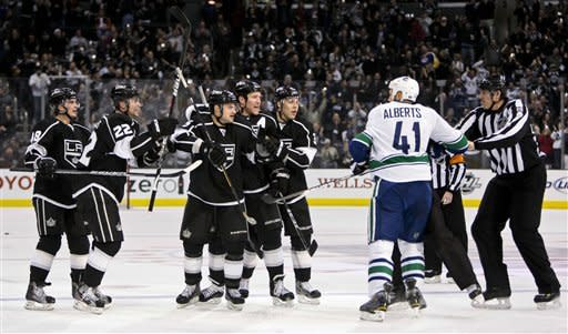 Vancouver Canucks defenseman Andrew Alberts (41) moves in to fight with members of the Los Angeles Kings after Kings defenseman Matt Greene, forth from the left, scored during the second period of an NHL hockey game, Saturday, Dec. 31, 2011, in Los Angeles. (AP Photo/Bret Hartman)