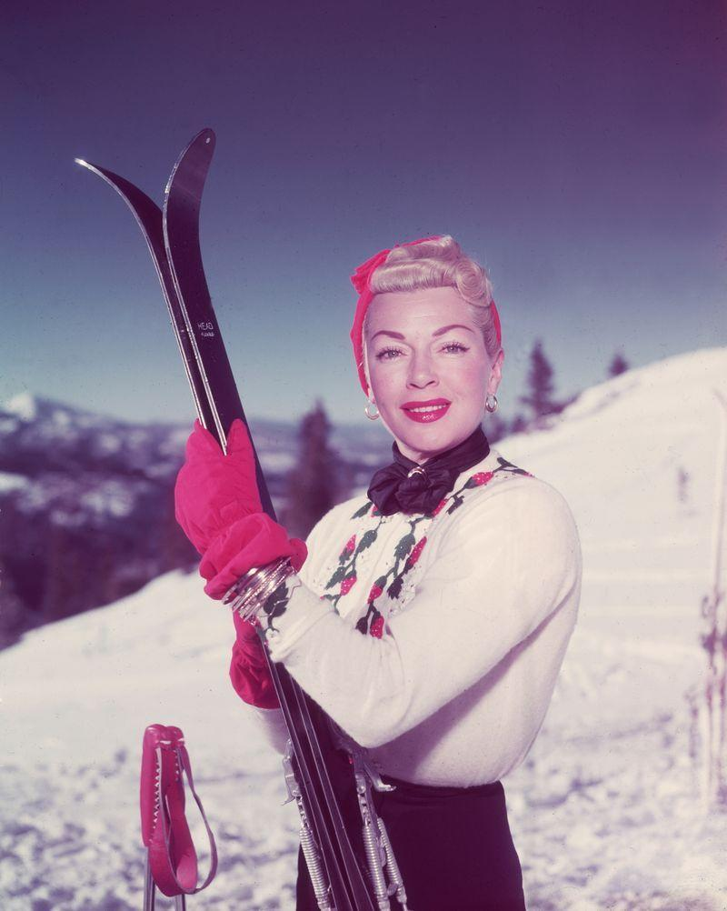<p>Lana Turner takes to the slopes for an alpine vacation in 1955. The American actress looks chic in a sweater, ski pants, and red winter accessories. </p>