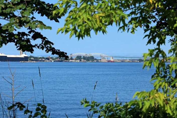 """<p><strong>Established in:</strong> 1668</p><p>Sault Ste. Marie is a port of entry and is linked to its <a href=""""https://www.britannica.com/place/Sault-Sainte-Marie-Michigan"""" rel=""""nofollow noopener"""" target=""""_blank"""" data-ylk=""""slk:Canadian twin city"""" class=""""link rapid-noclick-resp"""">Canadian twin city</a>, Sault Ste. Marie in Onatrio. It was first visited by French Canadian explorer Étienne Brûlé, and was named after the Virgin Mary. In 1668, Jacques Marquette founded a mission there. </p>"""