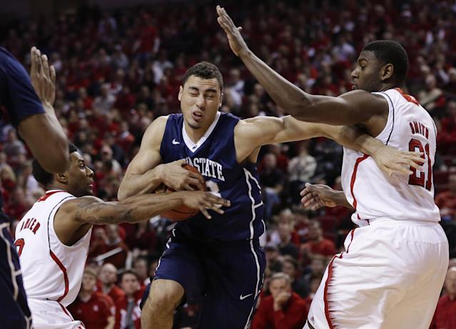 Penn State's Ross Travis, center, drives to the basket against Nebraska's Benny Parker, left, and Nebraska's Leslee Smith (21) in the first half of an NCAA college basketball game in Lincoln, Neb., Thursday, Feb. 20, 2014. (AP Photo/Nati Harnik)