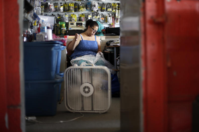 Maribel Castro sews in her un-air conditioned shop, Wednesday, July 17, 2013, in Philadelphia. An excessive heat warning is again in effect for the Philadelphia region with highs expected to head up to the mid-90s (AP Photo/Matt Rourke)