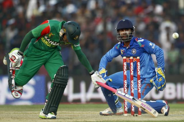 Bangladesh's captain Mushfiqur Rahim runs to avoid a run out as India's wicketkeeper Dinesh Karthik (R) breaks the wicket to dismiss him unsuccessfully during their Asia Cup 2014 one-day international (ODI) cricket match in Fatullah February 26, 2014. REUTERS/Andrew Biraj (BANGLADESH - Tags: SPORT CRICKET)