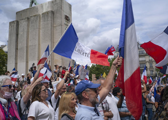 Thousands of protesters gather at Place Trocadero near the Eiffel Tower attend a demonstration in Paris, France, Saturday July 24, 2021, against the COVID-19 pass which grants vaccinated individuals greater ease of access to venues. (AP Photo/Rafael Yaghobzadeh)