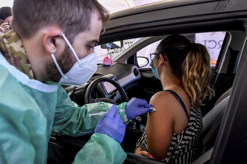 A health worker administers a dose of the AstraZeneca vaccine against COVID-19 to a patient at a drive-through vaccination center, in Milan, Italy, Monday, March 15, 2021. Half of Italy's regions have gone into the strictest form of lockdown in a bid to curb the latest spike in coronavirus infections that have brought COVID-19 hospital admissions beyond manageable thresholds. (Claudio Furlan/LaPresse via AP)