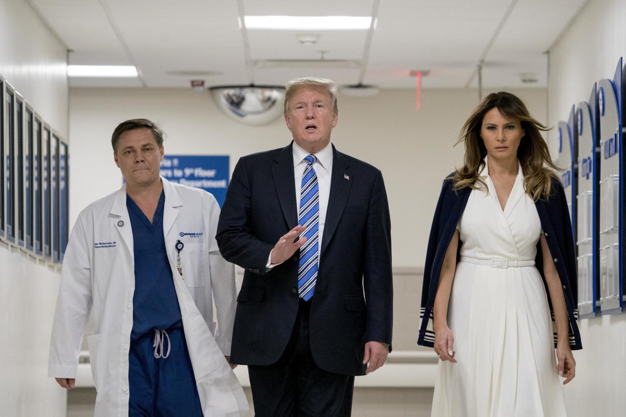 President Donald Trump, center, accompanied by and first lady Melania Trump, right, and Dr. Igor Nichiporenko, left, speak to reporters while visiting with medical staff at Broward Health North in Pompano Beach, Fla., Friday, Feb. 16, 2018, following Wednesday's shooting at Marjory Stoneman Douglas High School, in Parkland, Fla. (AP Photo/Andrew Harnik)