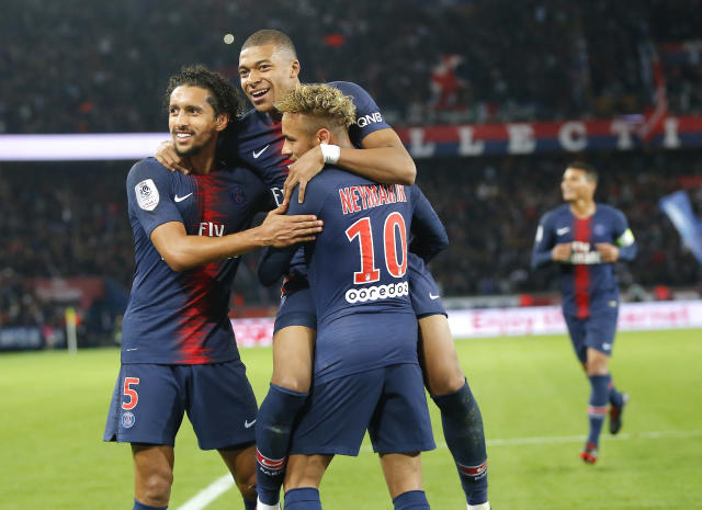 PSG's Kylian Mbappe celebrates with his teammate PSG's Neymar and PSG's Marquinhos, left, after scoring his side's fifth goal during the French League One soccer match between Paris-Saint-Germain and Lyon at the Parc des Princes stadium in Paris, France, Sunday, Oct. 7, 2018. (AP Photo/Michel Euler)