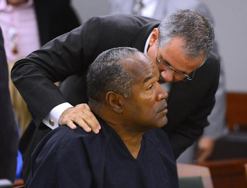 O.J. Simpson and his defense attorney Ozzie Fumo confer during an evidentiary hearing for Simpson in Clark County District Court on May 17, 2013 in Las Vegas. Simpson, who is currently serving a nine-to-33-year sentence in state prison as a result of his October 2008 conviction for armed robbery and kidnapping charges, is using a writ of habeas corpus to seek a new trial, claiming he had such bad representation that his conviction should be reversed. (AP Photo/Ethan Miller, Pool)