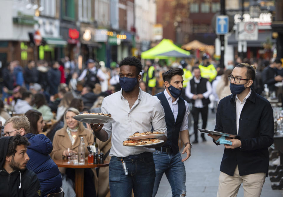 Waiters serve people eating and drinking at outside tables on Saturday evening, April 24, 2021, in Soho, central London, following the further easing of lockdown coronavirus restrictions in England. (Dominic Lipinski/PA via AP)
