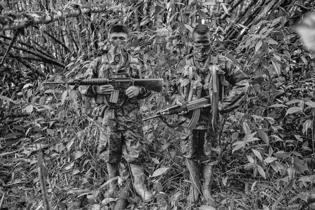 "<p>""Everybody Needs a Good Neighbor"": Colombia, Feb. 17, 2014. Angél 14, and Daniel (right), 16, members of the ELN Che Guevara Front, pose for a picture at their camp in Choc. The Che Guevara Front operates on the Pacific coast of Colombia, patrolling important corridors to allow the export of cocaine to the Pacific Ocean and into Mexico. (© Juan Arredondo from ""War Is Only Half the Story,"" the Aftermath Project & Dewi Lewis Publishing) </p>"