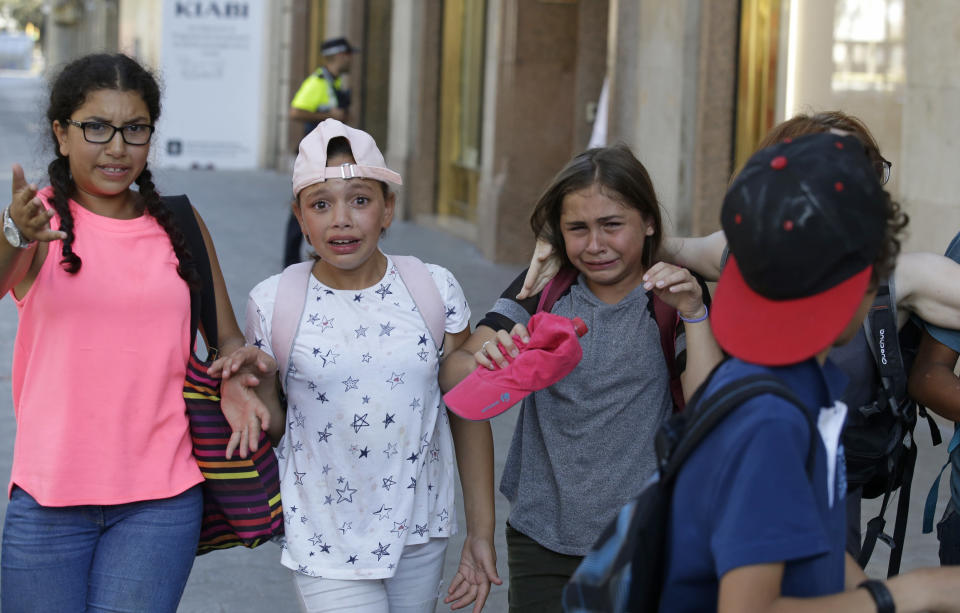 <p>Children, some in tears, are escorted down a road in Barcelona, Spain, Thursday, Aug. 17, 2017. Police in Barcelona say a white van has mounted a sidewalk, struck several people in the city's Las Ramblas district. (AP Photo/Manu Fernandez) </p>