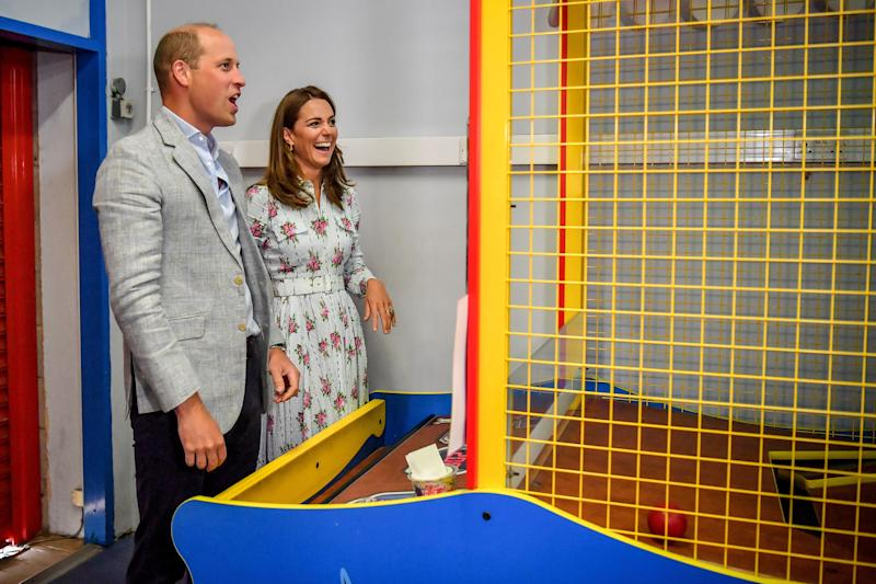 Prince William, Duke of Cambridge and Catherine, Duchess of Cambridge laugh after throwing balls to knock down figures on an arcade game at Island Leisure Amusement Arcade, where Gavin and Stacey was filmed, during their visit to Barry Island, South Wales, to speak to local business owners about the impact of COVID-19 on the tourism sector on August 5, 2020 in Barry, Wales.