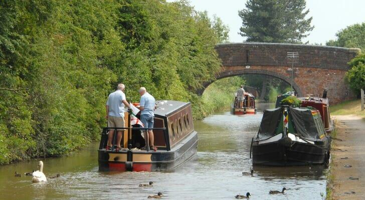 Two elderly men on a small barge traveling down a canal in Britain.