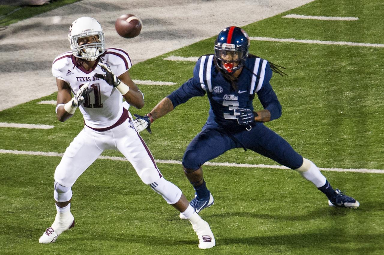 OXFORD, MS - OCTOBER 12: Wide receiver Derel Walker #11 of the Texas A&M Aggies prepares to catch a pass in front of defensive back Charles Sawyer #3 of the Ole Miss Rebels dunning the second half of play on October 12, 2013 at Vaught-Hemingway Stadium in Oxford, Mississippi. Texas A&M defeated Ole Miss 41-38. (Photo by Michael Chang/Getty Images)