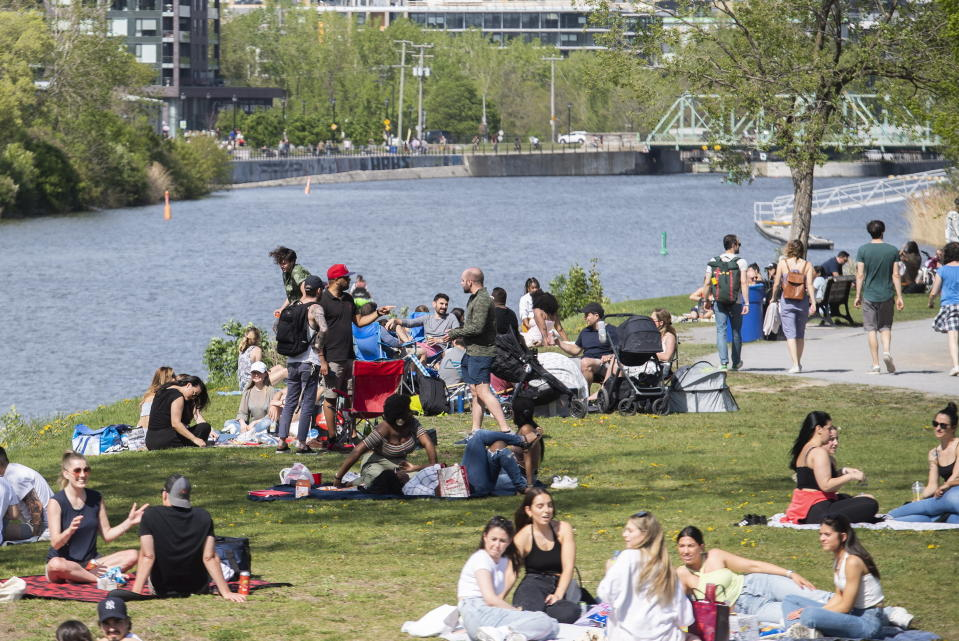 People gather next to the Lachine Canal on a warm spring day in Montreal, Saturday, May 15, 2021, as the COVID-19 pandemic continues in Canada and around the world. (Graham Hughes/The Canadian Press via AP)