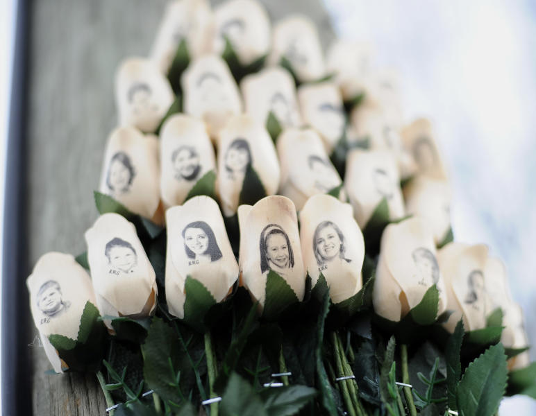 FILE - In this Jan. 14, 2013 file photo, white roses bearing the faces of victims of the Sandy Hook Elementary School shooting are displayed on a telephone pole near the school in Newtown, Conn. Adam Lanza opened fire inside the Sandy Hook Elementary School on Friday, Dec. 14, 2012, in Newtown, killing 26 students and educators. (AP Photo/Jessica Hill, File)