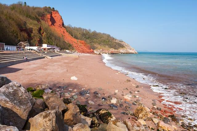 The red sandy beach and sandstone cliffs at Oddicombe Beach Torbay Devon England UK