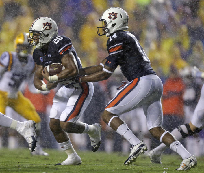 Auburn quarterback Nick Marshall (14) hands off to running back Corey Grant (20) in the first half of an NCAA college football game against LSU in Baton Rouge, La., Saturday, Sept. 21, 2013. (AP Photo/Gerald Herbert)