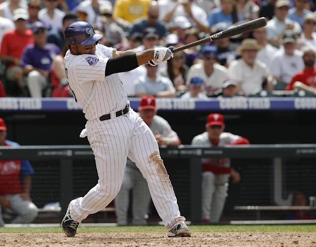 Colorado Rockies' Wilin Rosario follows through with his swing after connecting for an RBI-double against the Philadelphia Phillies in the fourth inning of a baseball game in Denver, Saturday, June 15, 2013. (AP Photo/David Zalubowski)