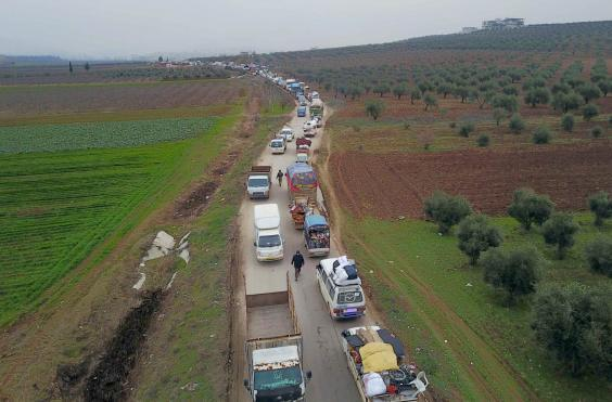 Civilians flee from Idlib to find safety inside Syria near the border with Turkey, 11 February 2020 (AP)