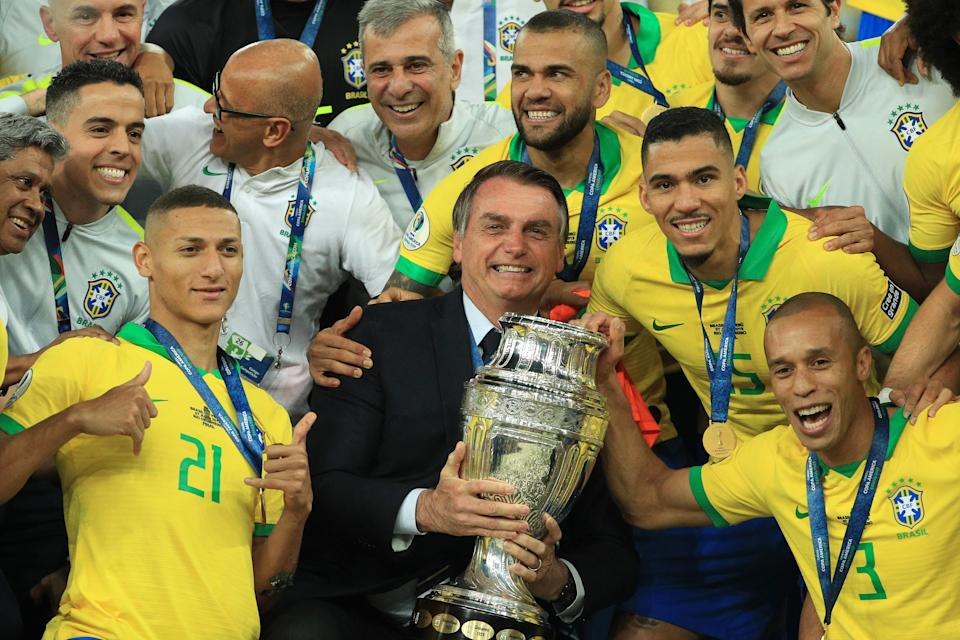 RIO DE JANEIRO, BRAZIL - JULY 07: President of Brazil Jair Bolsonaro celebrates with the trophy and the players of Brazil after winning the Copa America Brazil 2019 Final match between Brazil and Peru at Maracana Stadium on July 07, 2019 in Rio de Janeiro, Brazil. (Photo by Buda Mendes/Getty Images)
