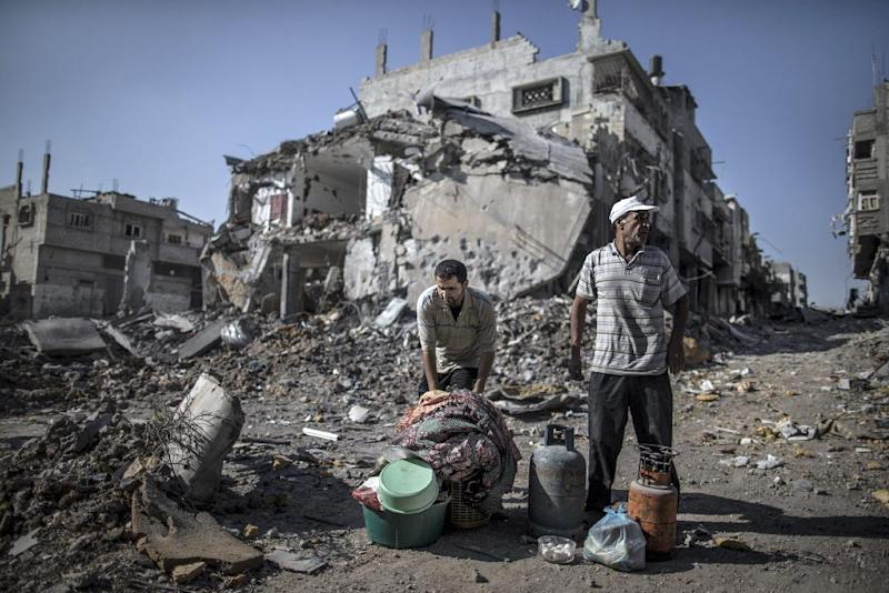 Palestinian men gather things they found in the rubble of destroyed buildings on July 27, 2014 in the Shejaiya residential district of Gaza City as families returned to find their homes ground into rubble by Israeli strikes (AFP Photo/Marco Longari )