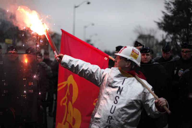 A worker of tire manufacturer Goodyear holds a flare as he faces French riot police during a demonstration in front the Goodyear headquarters, in Reuil Malmaison, outside Paris, Tuesday Feb. 12, 2013. U.S. tyremaker Goodyear confirmed in January to close a French plant near the northern city of Amiens, which would lead to the layoff of 1,173 jobs. (AP Photo/Thibault Camus)