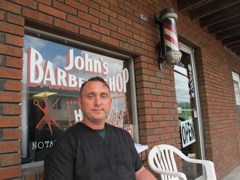 In this May 23, 2013, photo, barber BJ McClead, whose daughter Hayden was a friend of slain 16-year-old Skylar Neese, poses outside John's Barber Shop in Star City, W.Va. People in the small West Virginia town wondered for months about Neese. She vanished after slipping out the bedroom of her Star City home last summer, but few believed she'd run away. The truth emerged when one of Neese's friends admitted plotting with another teenage girl to kill her, a revelation that shocked even police. (AP Photo/Vicki Smith)