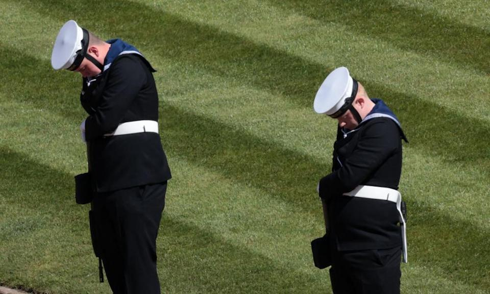 Members of the Royal Navy bow their heads outside St George's Chapel