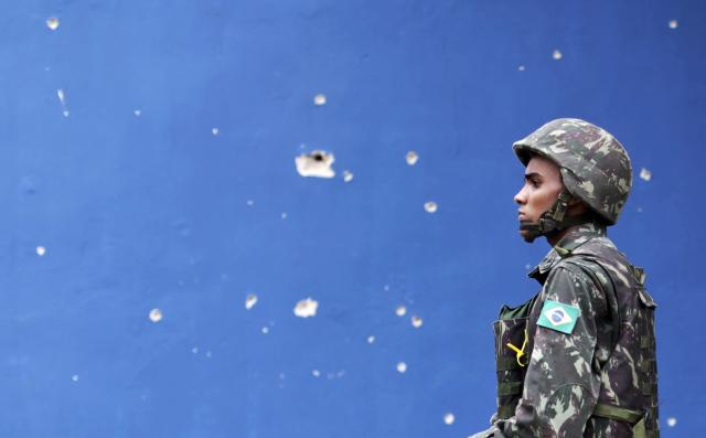 A Brazilian Army soldier walks past bullet holes in a wall during an operation in the Mare slums complex in Rio de Janeiro March 26, 2014. Brazil will deploy federal troops to Rio de Janeiro to help quell a surge in violent crime following attacks by drug traffickers on police posts in three slums on the north side of the city, government officials said on Friday. Less than three months before Rio welcomes tens of thousands of foreign soccer fans for the World Cup, the attacks cast new doubts on government efforts to expel gangs from slums using a strong police presence. The city will host the Olympics in 2016. REUTERS/Ricardo Moraes (BRAZIL - Tags: CRIME LAW)