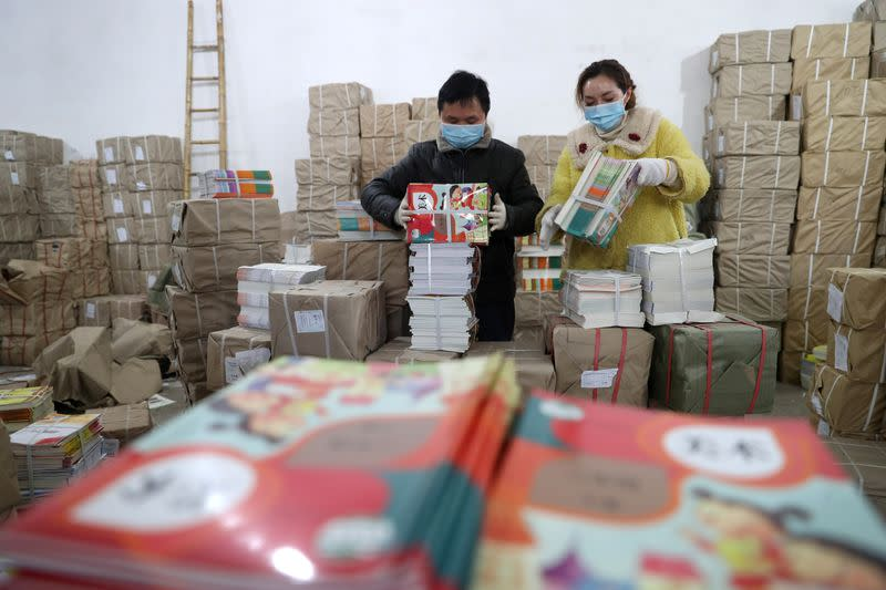 Workers wearing face masks sort textbooks at a warehouse for Xinhua Bookstore, after students' return to school was delayed due to the novel coronavirus outbreak, in Fuzhou