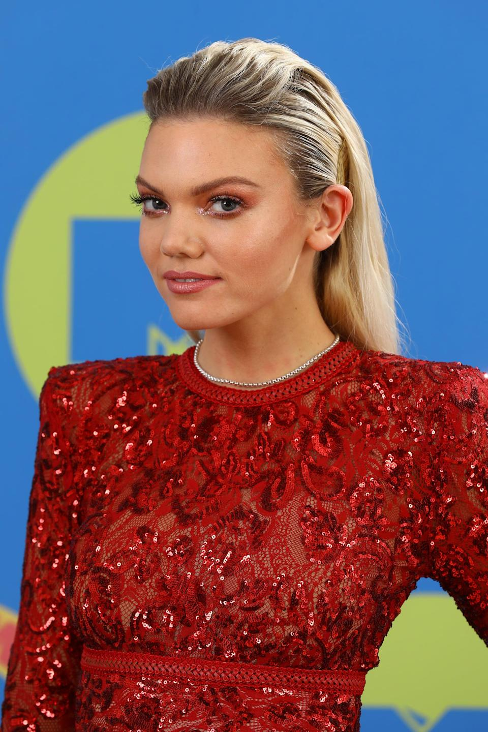 <p>Becca Dudley, MTV's preshow presenter, matched her eyeshadow and lips to her beautiful red jumpsuit and finished the look off with a brushed-back wet-look hairdo.</p>