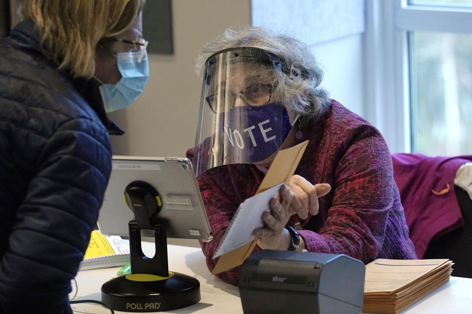 Poll worker Alice Machinist, of Newton, Mass., right, wears a mask and shield out of concern for the coronavirus while assisting a voter, left, with a ballot during early in-person general election voting, Wednesday, Oct. 28, 2020, at the Newton Free Library, in Newton, Mass. (AP Photo/Steven Senne)