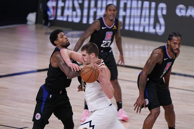 Denver Nuggets center Nikola Jokic (15) drives against Los Angeles Clippers guard Paul George (13) during the second half of an NBA conference semifinal playoff basketball game Tuesday, Sept. 15, 2020, in Lake Buena Vista, Fla. (AP Photo/Mark J. Terrill)