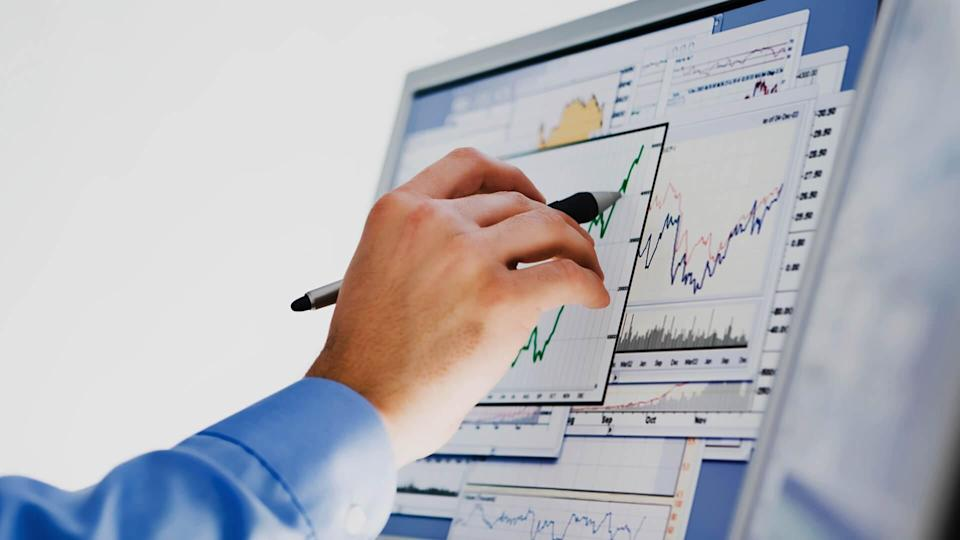 Businessman researching stock market data on computer monitor.