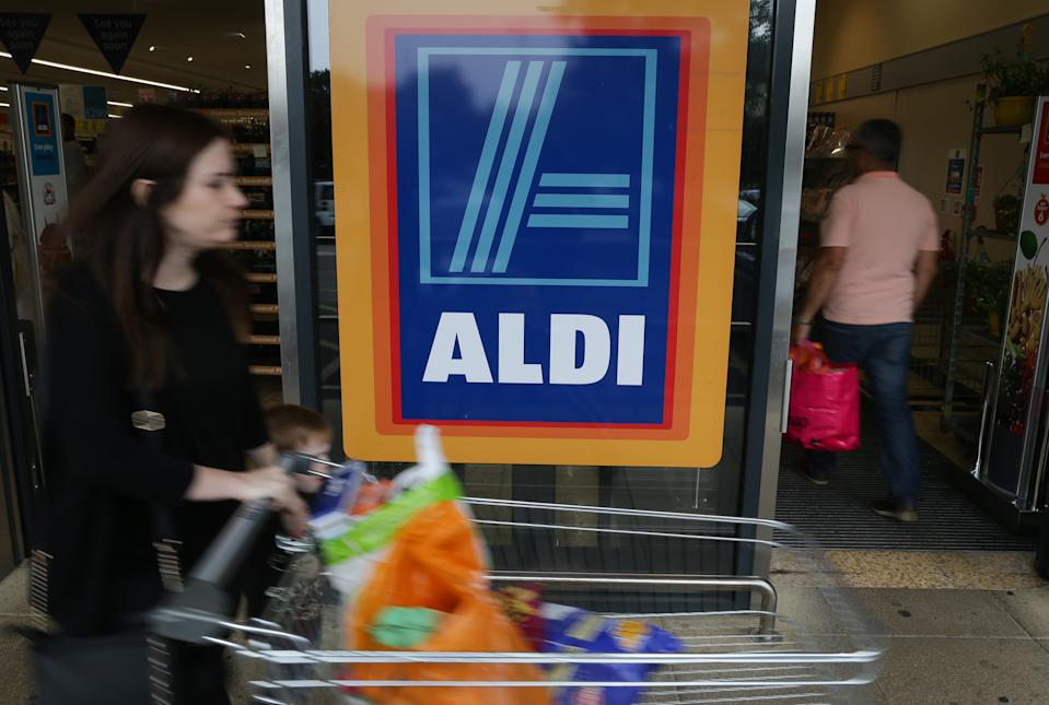 A woman pushes a shoping trolley past an Aldi logo as she leaves one of the company's supermarket stores in London on September 26, 2016. Aldi UK announced on Monday that it will invest £300 million ($389 million, 346 million euros) to revamp its stores over the next three years. Aldi and its German rival Lidl have boomed in Britain, grabbing market share from traditional supermarkets Asda, Morrison, Sainsbury's and Tesco, as customers tightened their belts to save cash. / AFP / Daniel Leal-Olivas        (Photo credit should read DANIEL LEAL-OLIVAS/AFP/Getty Images)