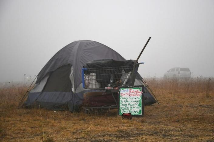 "A sign in front of a tent along the highway near Salem, Oregon on September 13, 2020 reads ""Lost Everything Due To House Fire"""